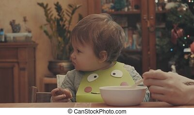 Someone feeding the baby soup, and she eating bread. Eye...