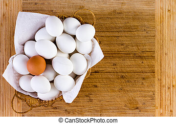 Basketful of clean white eggs with one brown one