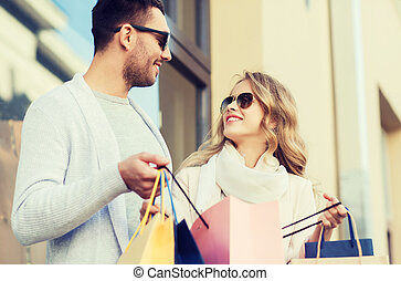 happy couple with shopping bags on city street - sale,...