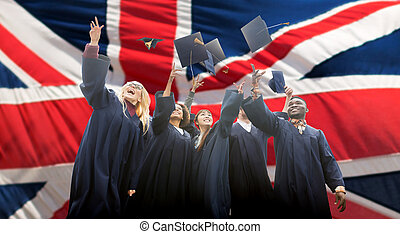 happy students throwing mortarboards up - education,...