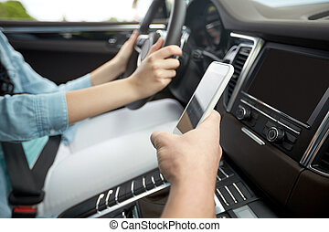 happy man and woman with smartphone driving in car - road...