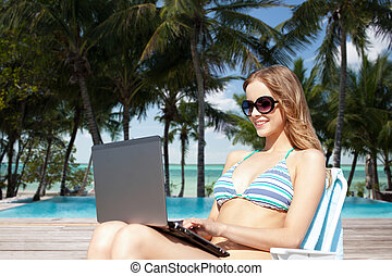 woman with laptop sunbathing in lounge on beach - summer...