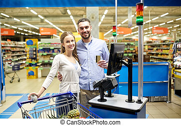couple buying food at grocery store cash register -...
