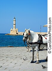 Horse drawn carriage and lighthouse, Chania. - Horse drawn...