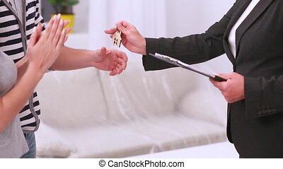 Estate agent giving key to couple - Estate agent woman...