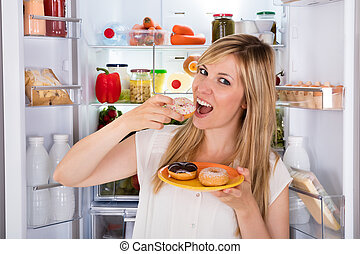 Woman Eating Sweet Donut Near Refrigerator