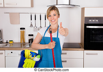 Housemaid Showing Thumbs Up In Kitchen - Cleaning Service...