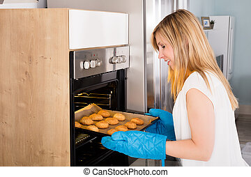Smiling Woman Placing Cookies In Oven
