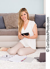 Young Woman Calculating Tax At Home