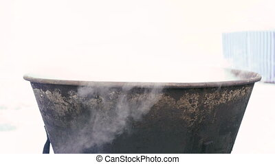 Boiling water in a pots above the fire.