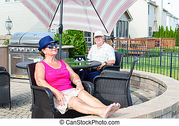 Elderly couple relaxing on an upmarket patio - Elderly...