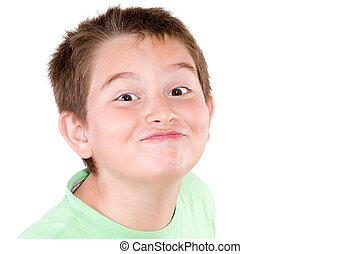 Playful mischievous young boy pulling a cute funny face at...