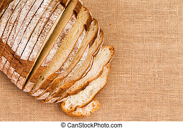 Burlap tablecloth under sliced artisan bread - Close up of...