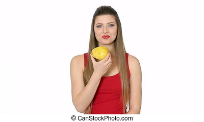 beautiful girl eats ripe pear on white background -...