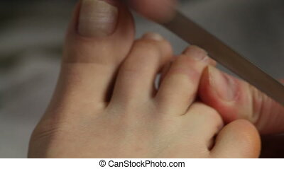 Woman getting pedicure in nail salon - Beautician filing...