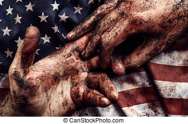 Human hands in blood and dirt on american flag