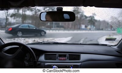 Driving car during snow - Beautiful woman travelling by car...