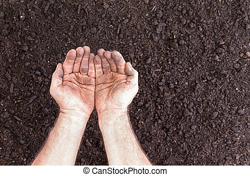 Pair of empty hands holding nothing over bare soil for...