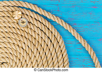 Thick rope and open directional compass over blue painted...