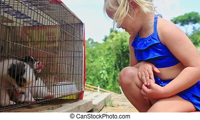 Little Blond Girl with Pigtail Watches Puppies in Cage