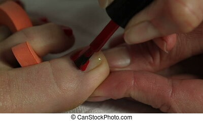 Woman getting pedicure in nail salon - Beautician polishing...