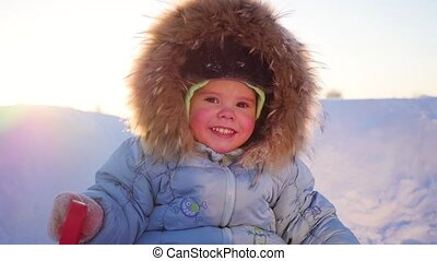 happy child with fun laughing in winter park on a sunny day....