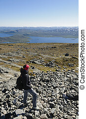 Hiking in Lapland - Girl wearing hiking clothes walking a...