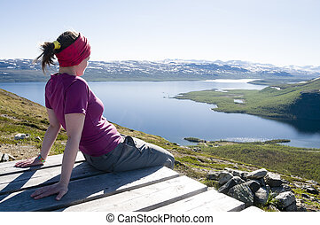 Watching Lapland landscape - Girl sitting on the top of...