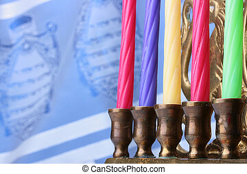 Menorah candles in front of a blue and white tallit. Add...