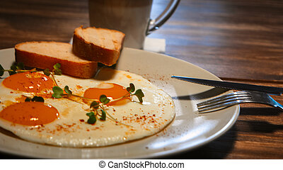 Fried eggs with bread in a plate on a wooden table, selective focus, side angle view