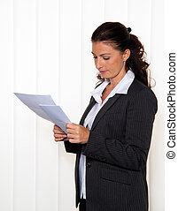 Businesswoman reading a letter in the office. News of the...