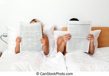 Couple in bed reading a newspaper. Information and news - A...