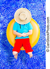 Happy young boy relaxing on a tube in the pool