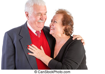 Happy seniors with arms around each other smile against a...