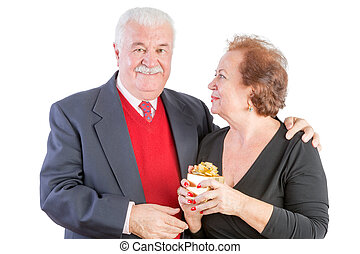 Senior with one arm around his lady friend smiles at the...