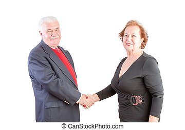 Elderly business man and woman shake hands and smile at the...