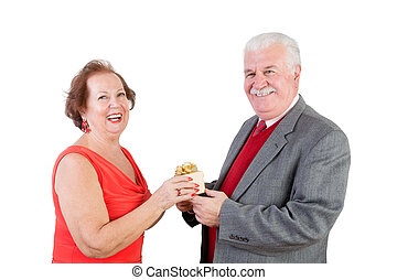 Elderly couple exchange a valentine gift and smile at the...
