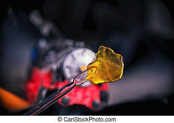 Cannabis oil concentrate aka shatter (train wreck strain) with dabbing tool