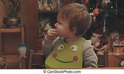 Little baby eating bread. Eye level shot, 4K