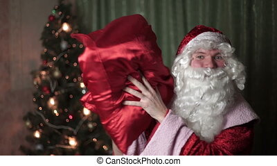 Closeup portrait of Santa Claus with a red bag of gifts, new year, christmas