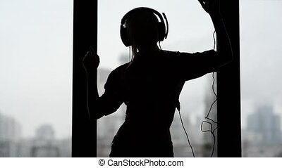 Sexy, happy woman listening to music and dancing