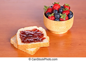 Two toast with jam, blueberries and strawberries in a bowl...