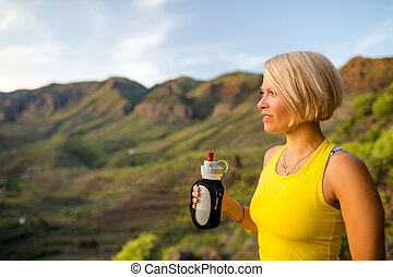 Happy woman trail runner drinking water in mountains