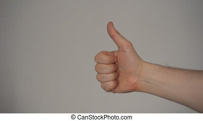 Man show thumbs up with his hand at plain light background