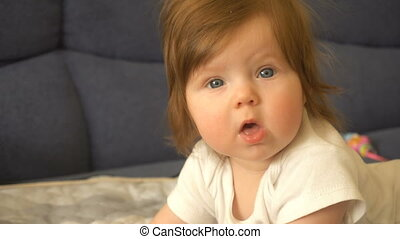 A cute little baby girl is looking into the camera. Very...