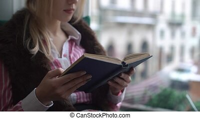 Beautiful young woman sitting on the windowsill, reading a book and looks out the window