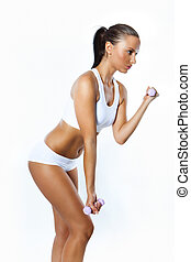 Portrait of fitness woman working out with free weights in...