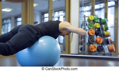 Female trainer in the gym doing hyperextension relying on fitball.