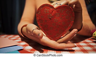 Close-up Female holding red heart in her hands, love symbol