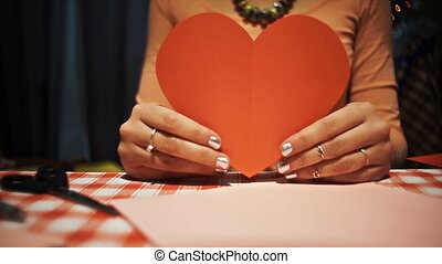 Close-up Female tearing heart valentines card in her hands,...